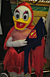 Daisy Duck dressed in a red riding hood costume and holding a Supergirl costume.